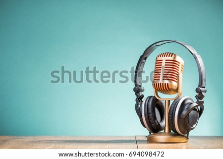 Retro golden microphone and headphones on table front gradient aquamarine background. Vintage old style filtered photo