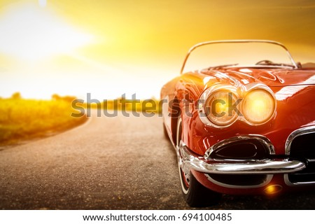 retro car on road and golden autumn space  Royalty-Free Stock Photo #694100485