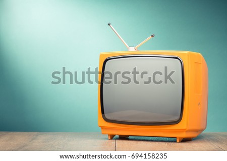 Retro old orange TV receiver on the table front textured gradient mint green background. Vintage style filtered photo