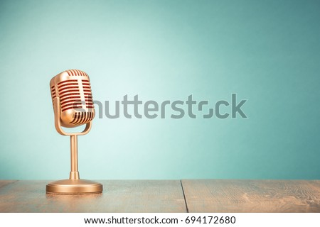 Retro golden microphone for press conference or interview on table front gradient mint green background. Vintage old style filtered photo #694172680