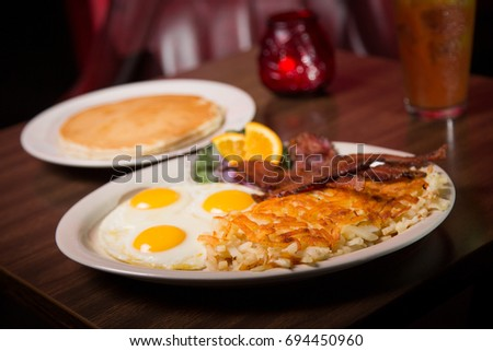 Low angle close up of traditional American roadside diner breakfast of three sunny side up fried eggs and potato hash browns with bacon strips and buttermilk pancake side at retro brunch restaurant #694450960