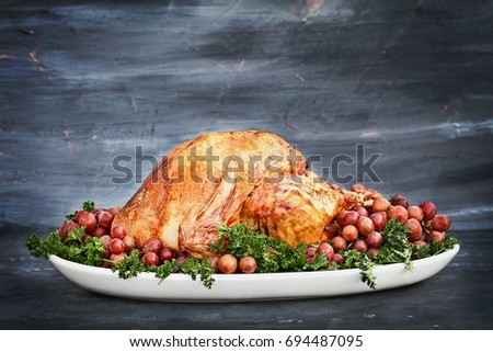 Delicious golden roasted Thanksgiving turkey  on a platter garnished with parsley and fresh grapes against a rustic background.