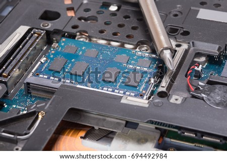 Close up of a screwdriver and electrical parts and components of a laptop computer in a maintenance themed concept. #694492984