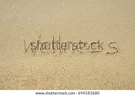Wellness concept. The word Wellness written on sand. #694583680