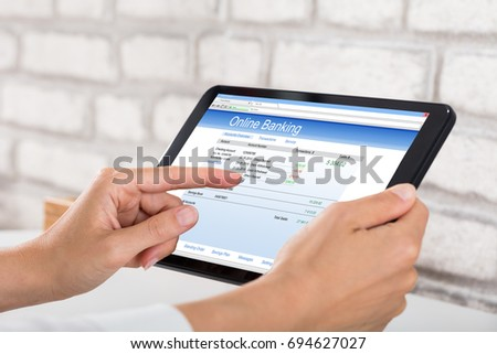 Close-up Of A Businesswoman Doing Online Banking On Digital Tablet #694627027