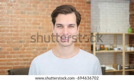 Portrait of confident young man smiling and  standing in his office #694636702
