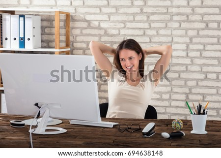 Happy Young Businesswoman Stretching Her Arms At Workplace #694638148