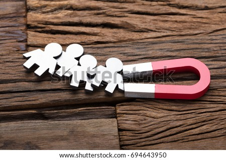 High angle view of magnet attracting traffic on wooden table Royalty-Free Stock Photo #694643950