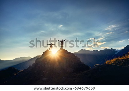 Two Hikers in silhouette stands on the rock in the beautiful mountains with rising hands at sunrise sky background Royalty-Free Stock Photo #694679659