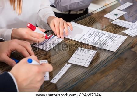 Designers Developing Mobile Application On Paper Over Desk #694697944