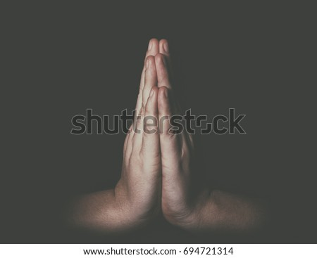 Man hands in praying position low key image Royalty-Free Stock Photo #694721314