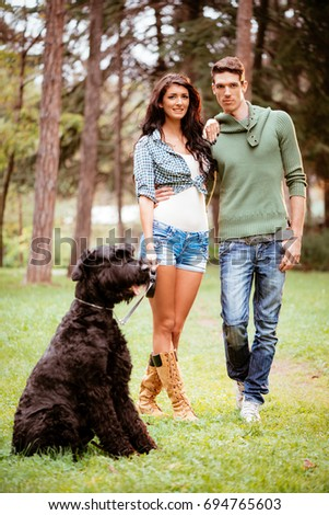 Beautiful lovely couple with a black giant schnauzer enjoying in the park. #694765603