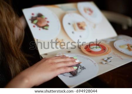 Menu card in woman's hand #694928044