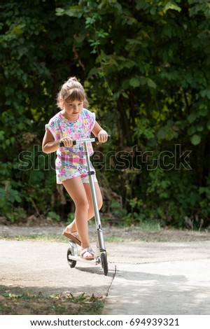 Little girl enjoys riding scooter #694939321