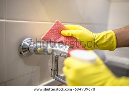 Cleaning the faucet. Young handsome man wiping faucet in kitchen. House cleaning service or husband doing chores #694939678