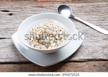 Healthy breakfast of boiled job's tears porridge in white bowl and spoon #695072521