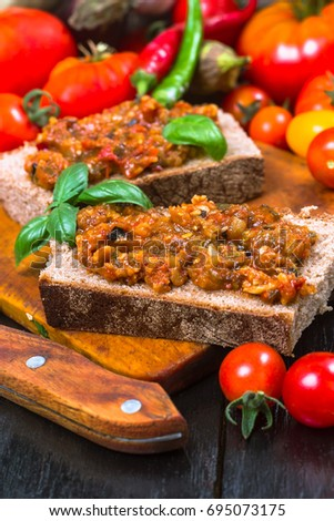 Spicy appetizer on a piece of black bread with a background of tomatoes and vegetables #695073175