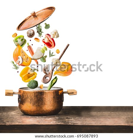Healthy vegetarian eating and cooking with various flying chopped vegetables ingredients, cooking pot and  spoon at wooden table desk , isolated on white background, front view. Clean food concept #695087893