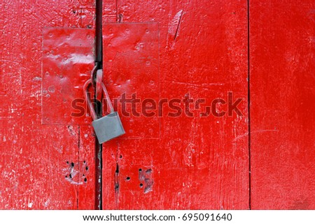 The old steel lock on the old red door, with a space for caption.