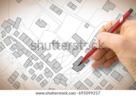 Hand drawing an imaginary cadastral map of territory with buildings and roads #695099257