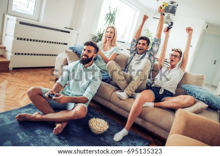 Beautiful couples playing video games on console ,having fun with beer and popcorn. #695135323