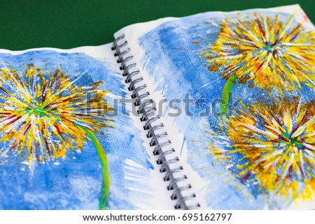 An old calender with spiral binding has been made into an art journal for mixed media art. It is used for experimenting with different media and techniques. Acrylic painting of flowers.