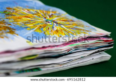 An old calender with spiral binding has been made into an art journal for mixed media art. Viewed from the side to show the wavy pages. Shallow depth of field.