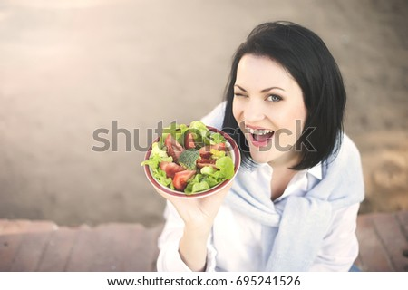 Young woman sitting on the green grass, winks and eating green salad #695241526