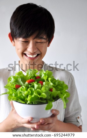 Chinese looks young woman smiling to her healthy salad bowl #695244979