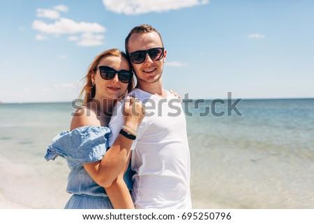 Young traveling couple walking along sandy beach near the sea #695250796