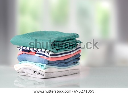 Stack of clothes on table indoor.Household concept.Fresh folded cotton clothing. #695271853