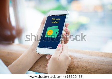 Bitcoin wallet.close-up of female hands holding mobile phone #695320438