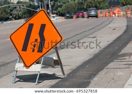 Orange and black merging lanes sign on city street. Moving cars and construction drums in blurred background.