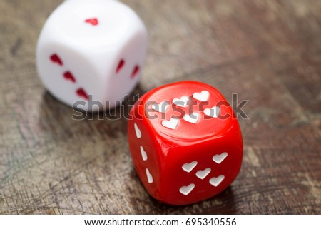 two dices with hearts on wooden table #695340556