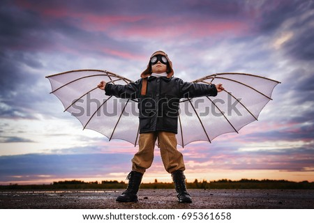 Boy with wings at sunset imagines himself a pilot and dreams of flying Royalty-Free Stock Photo #695361658