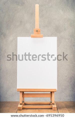 Portable desk easel for painting with canvas blank on wooden table front concrete wall background. Retro instagram old style filtered photo