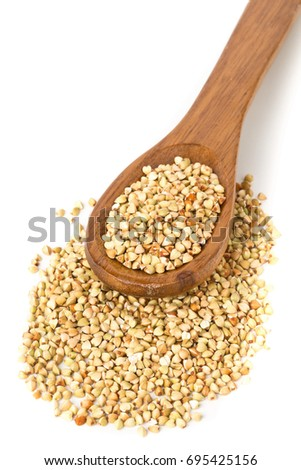 Raw, natural, uncooked buckwheat seed kernels in wooden spoon over white background #695425156