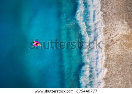 Aerial view of young woman swimming on the pink swim ring in the transparent turquoise sea in Oludeniz,Turkey. Summer seascape with girl, beautiful waves, azure water in sunny day. Top view from drone #695440777