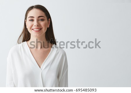 Portrait of happy beautiful young businesswoman smiling looking at camera over white background. #695485093
