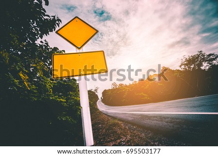 Traffic sign placed beside along the road. The steep hill ascent road and the traffic sign label beware for high-speed driving. #695503177