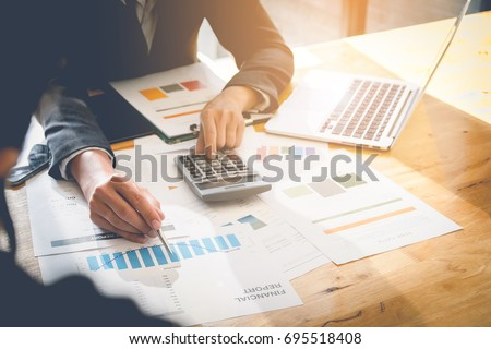 Consult financial concept. Business man pointing at papwework and using laptop computer. #695518408