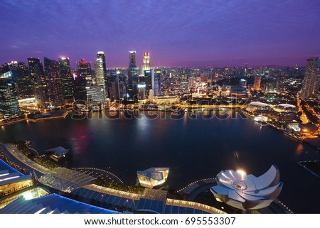 Singapore - JUNE 20 2017: Singapore city view from roof of Marina Bay Hotel in purple twilight sky color #695553307