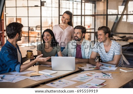 Beautiful young business people in casual clothes are using a laptop, talking and smiling while working in office #695559919