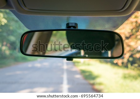 Vehicle interior with rear view mirror and windshield - car salon concept Royalty-Free Stock Photo #695564734