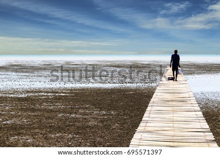 Man walking at boardwalk to sea,Thailand. #695571397