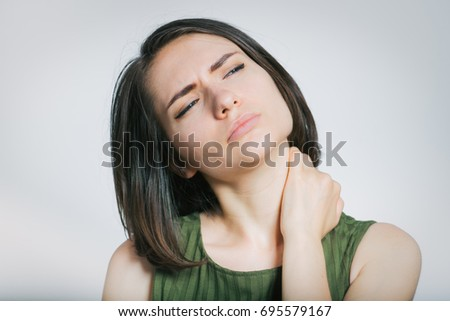 The woman has a sore neck, isolated on a gray background