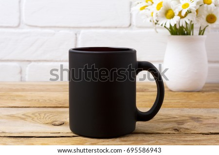 Black coffee mug mockup with white field chamomile bouquet in handmade rustic vase. Empty mug mock up for brand promotion. #695586943