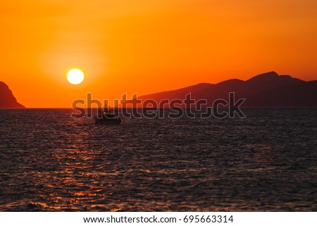 Sunrise with small boat Silhouette #695663314