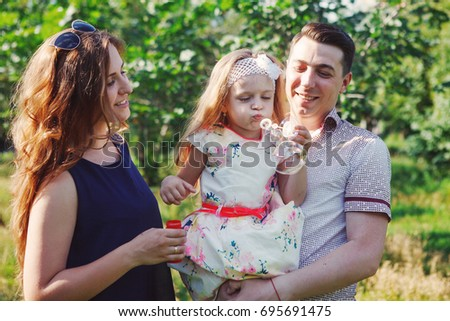 Little girl with parents playing in the Park, blowing bubbles. Happy family laughing. #695691475