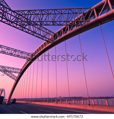 road through the bridge with blue sky background of a city. #69570673